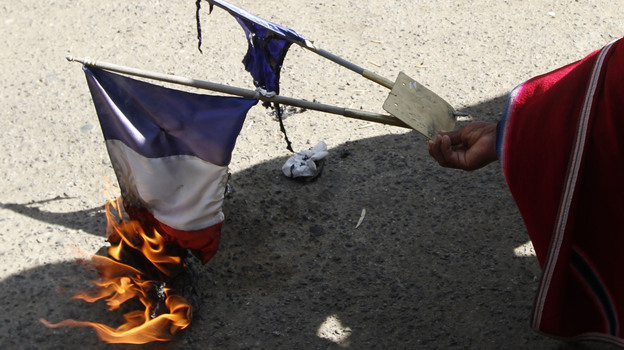 A man burns the French flag outside France's embassy in La Paz, Bolivia, Wednesday. Bolivia's President Evo Morales is returning home late today, after his plane was not allowed to fly in the airspace of France and other countries. (AP)