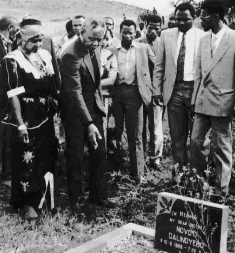 In 1990, Nelson Mandela (wearing a dark suit, pointing down) visited the graves of family members in Qunu, South Africa. A grandson's 2011 decision to move some relatives' remains to another site was followed by a lawsuit and court action.