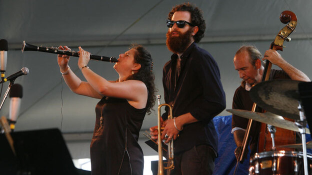 Anat Cohen (left) performs with Avishai Cohen (center) at the Newport Jazz Festival. (Ayano Hisa for NPR)