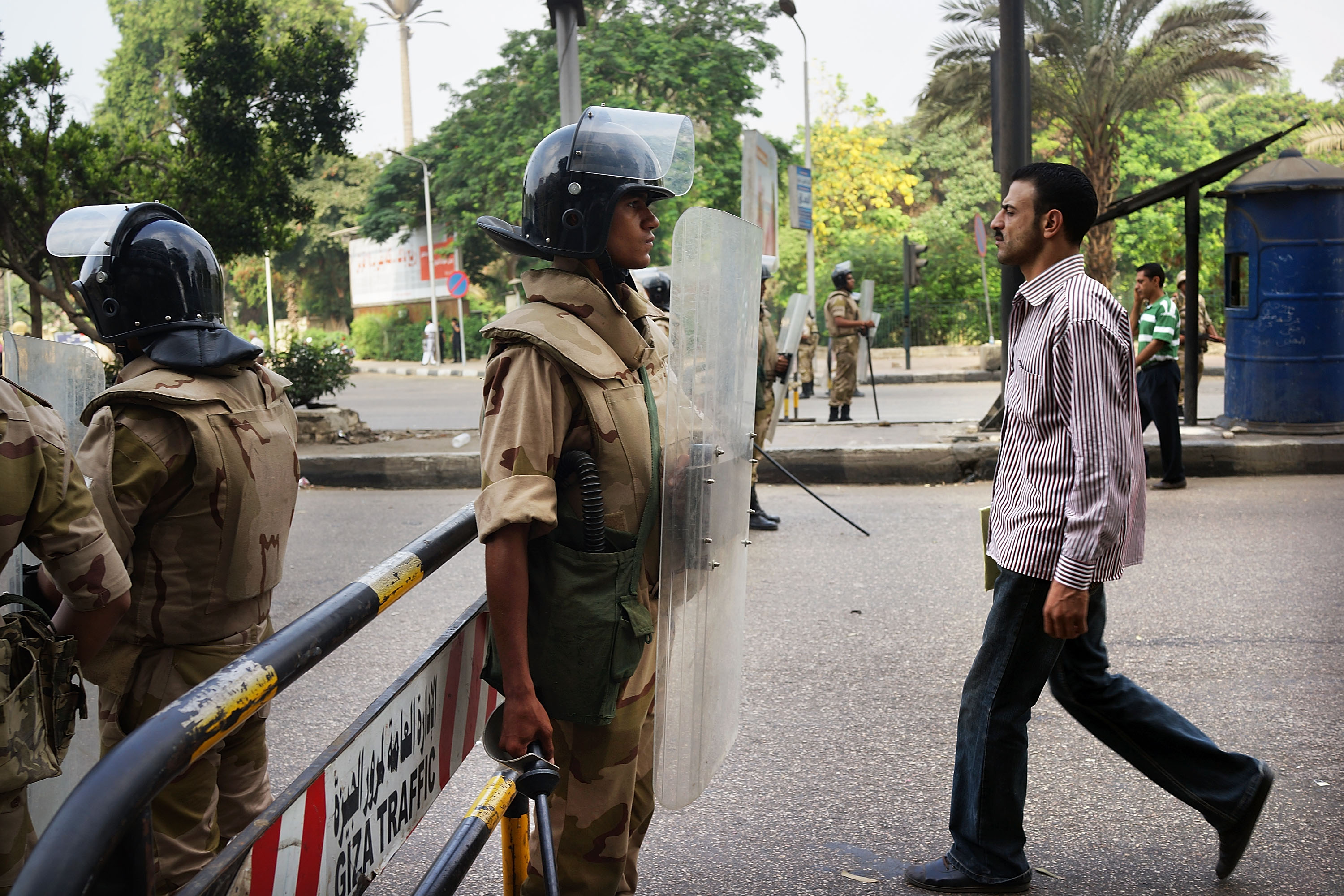Pedestrians walk by members of the Egyptian military as they stand guard at a roadblock in Cairo's Giza district.