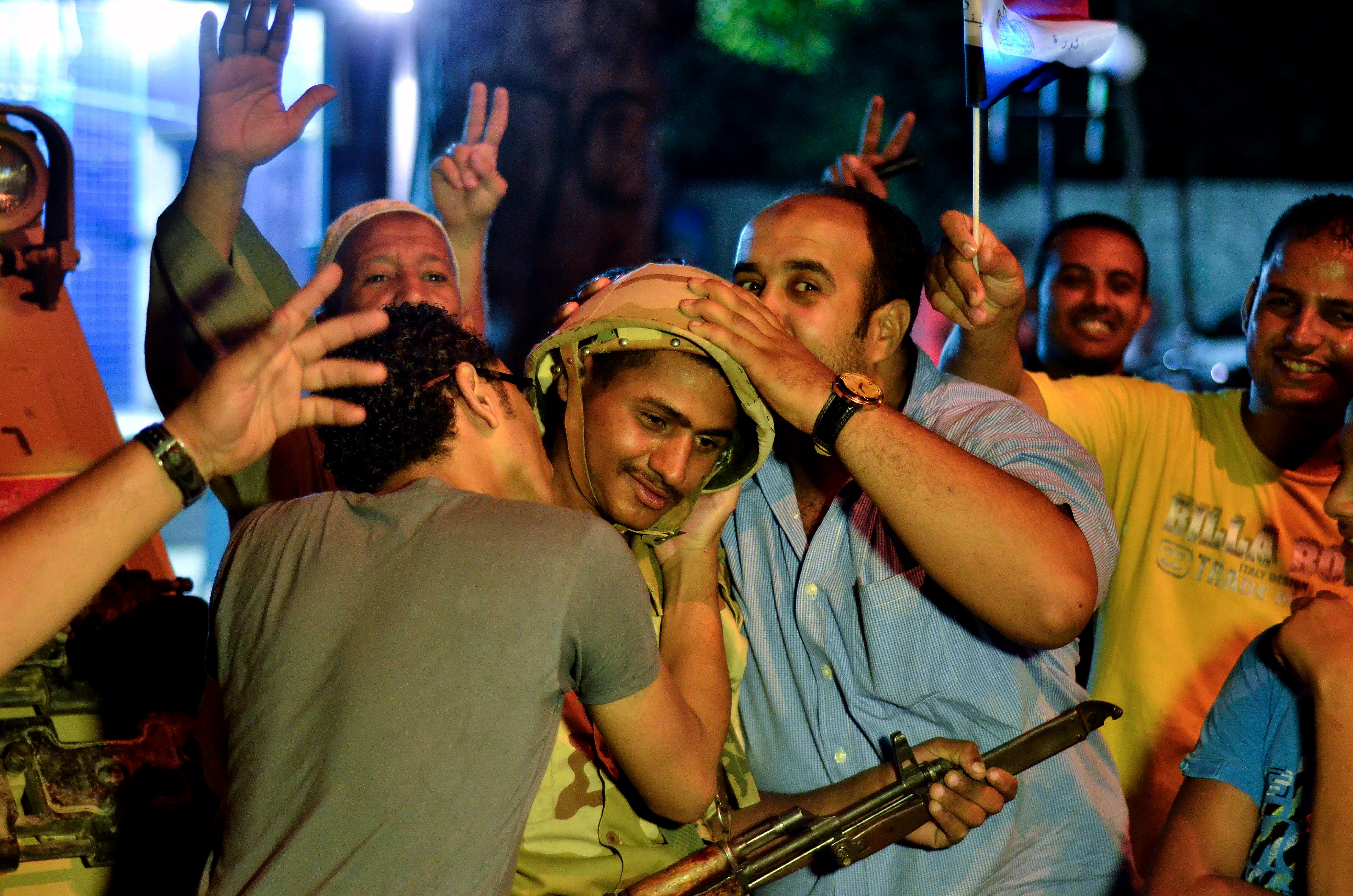 Egyptians hug and kiss an army soldier. The military has expressed concern about limiting violence following news of Wednesday's coup.