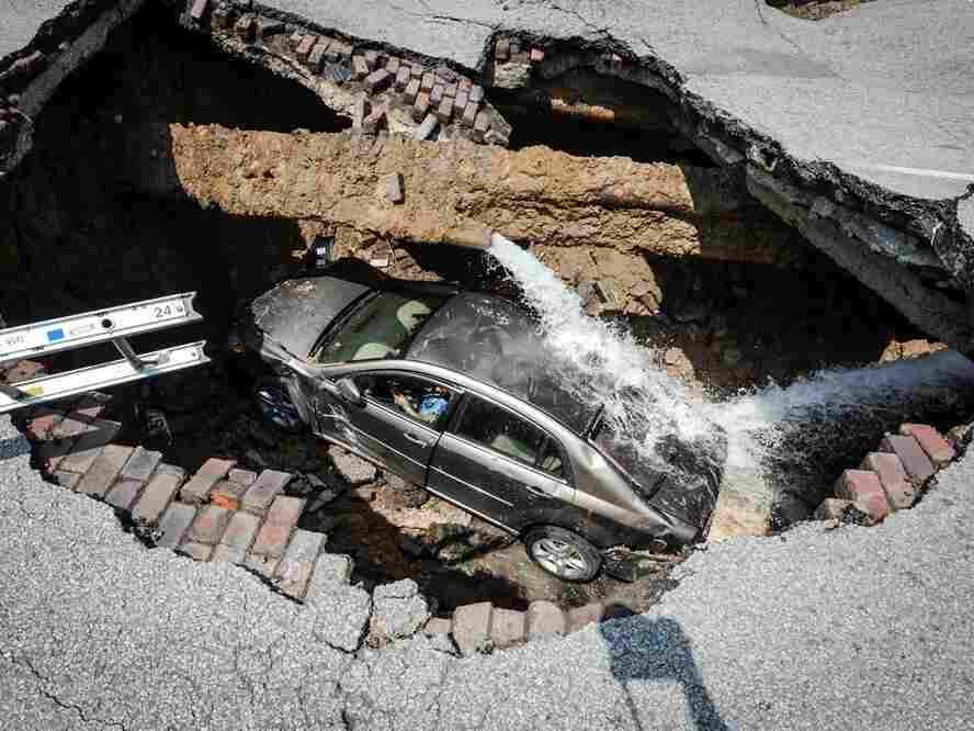 Quite a drop: Pamela Knox (in driver's seat) and her car dropped into a massive sinkhole Wednesday in Toledo. She was not injured.