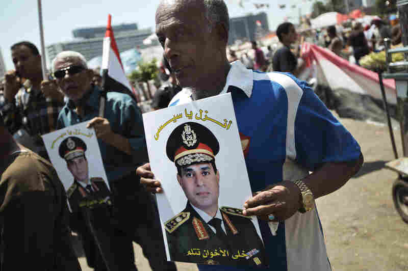 "Egyptians hold portraits of military chief General Abdel Fattah al-Sissi reading in Arabic ""Come down Sisi, let the Muslim Brotherhood stay silent"" as they gather in Cairo's Tahrir Square on July 5. With its popularly supported overthrow of president Mohamed Morsi, Egypt's army has placed itself at the forefront of a difficult transition."