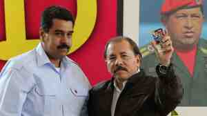 Nicaraguan President Daniel Ortega (right) and his Venezuelan counterpart Nicolas Maduro stand in front of a picture of late Venezuelan President Hugo Chavez, during a summit in Managua on June 29.