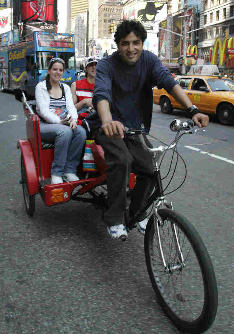 A pedicab rider takes tourists on a ride through Times Square in 2006.