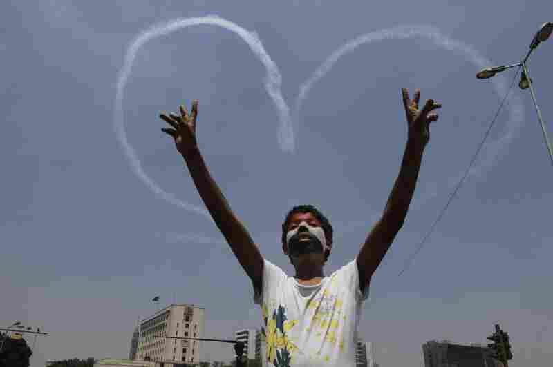An Egyptian protester flashes v signs for military aircrafts forming a heart shape trails in the sky over Tahrir Square in Cairo, Egypt, on Friday, July 5. Egypt's Muslim Brotherhood called for a wave of protests Friday, furious over the military's ouster of its president.