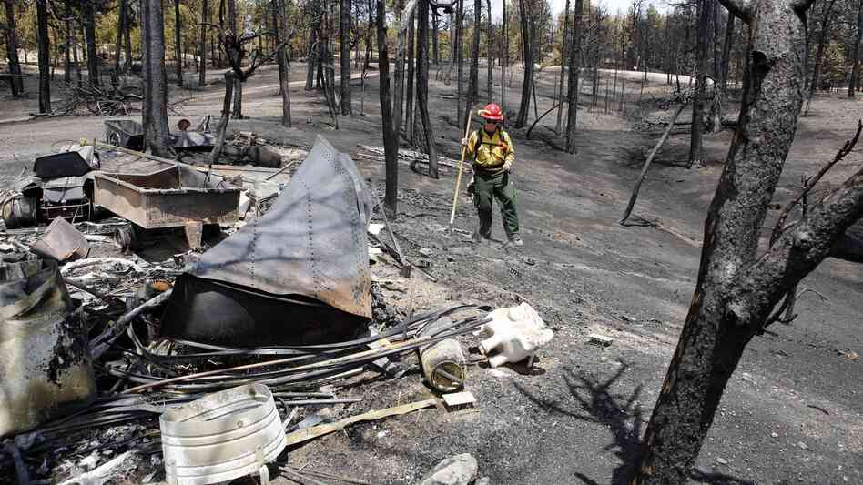 Firefighter Brandie Smith walks by the remains of a structure destroyed in the Black Forest wildfire north of Colorado Springs last month. More than 500 homes have been lost to wildfire in the stat