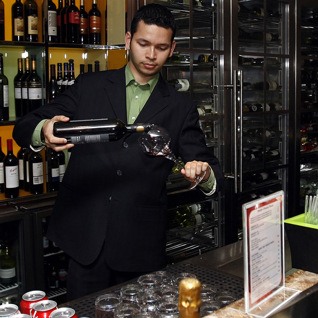 A waiter pours a drink at a bar in Dubai in 2011. In the United Arab Emirates, foreign residents may obtain permits to buy alcohol from a handful of designated stores. Booze is also available in licensed hotels and pubs. Locals, yet again, are out of luck.