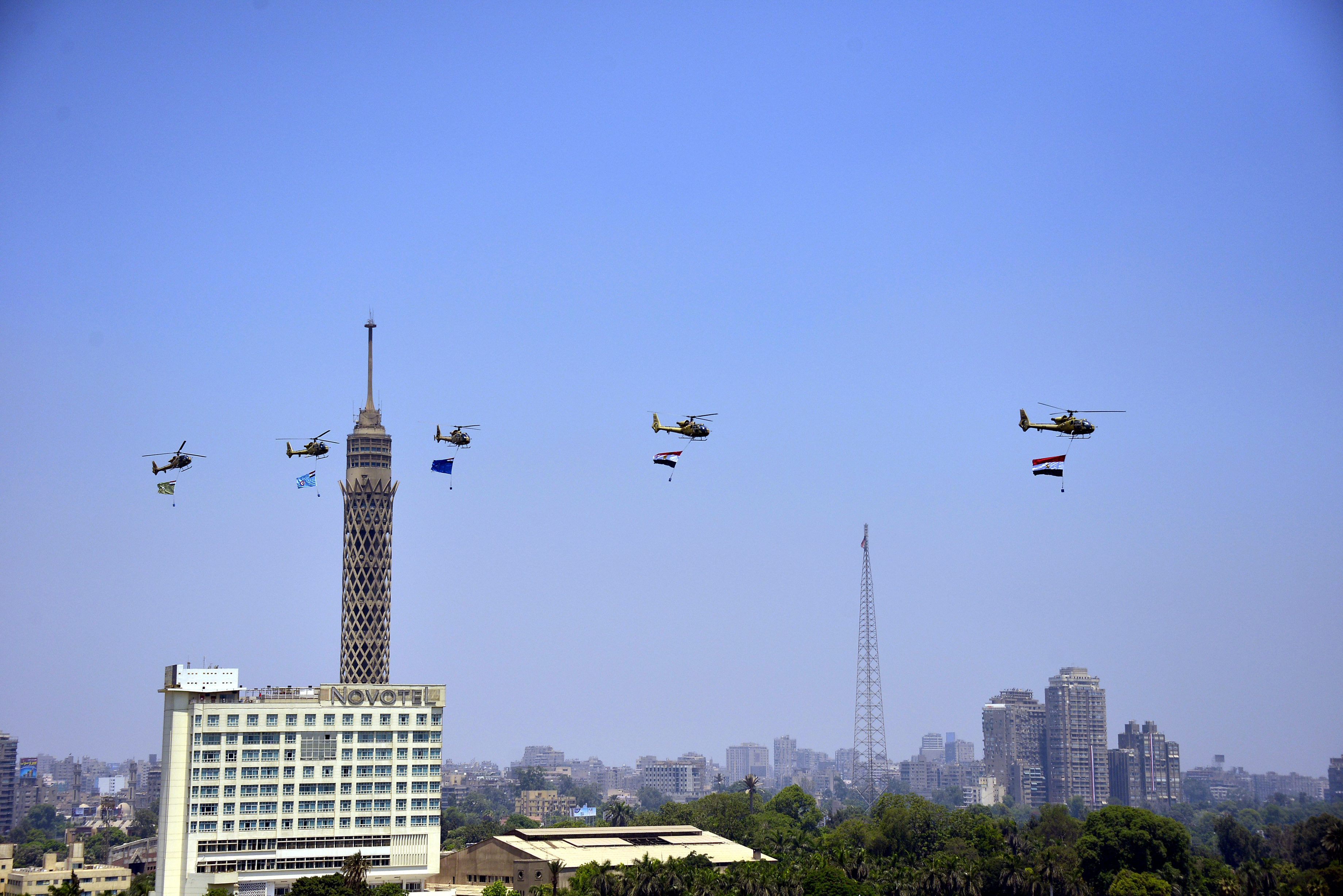 Egyptian army helicopters fly over Cairo with the national flags. Clashes between Muslim Brotherhood supporters and opponents have raised fears of deadly violence over the military's decision to depose and arrest Morsi, Egypt's first democratically elected president.