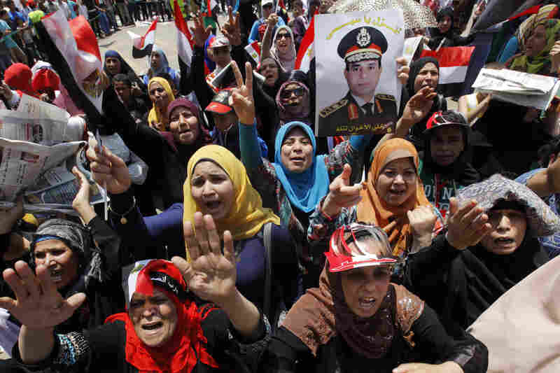 "Opponents of Morsi wave national flags and posters of Egypt's military chief, Lt. Gen. Abdel-Fattah el-Sissi, during a protest in Tahrir Square. The signs, in Arabic, read, ""Sissi, get in."""