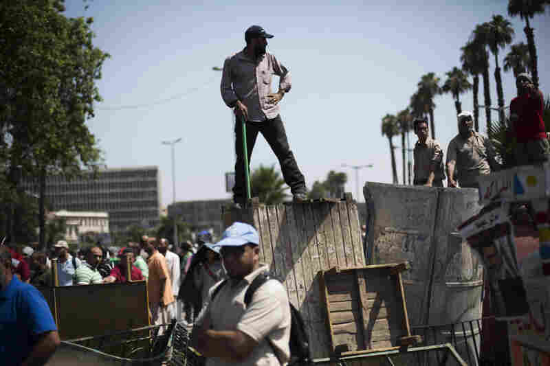 "A Morsi supporter stands guard on top of a barricade during a rally at Cairo University in Giza. Tens of thousands of Morsi supporters chanted ""Down with military rule."""