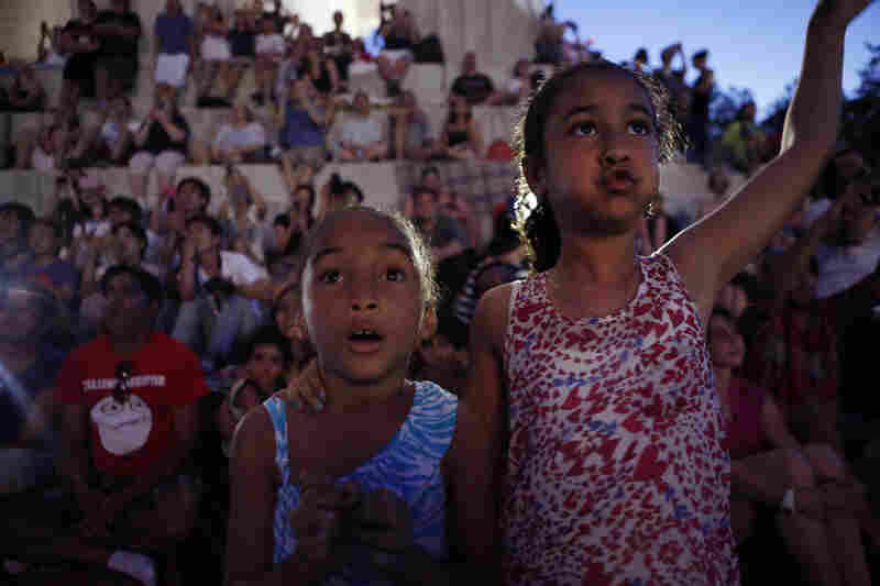 Emanuyani Yamni (left) and her sister Kaiar, both of Rochester, N.Y., enjoy the fireworks over the reflecting pool at the Lincoln Memorial on July Fourth.