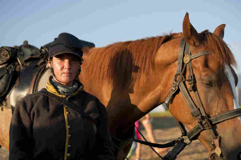 Brandi Cole, of Ohio, trains horses to be ridden in a cavalry unit, working with them so they become accustomed to the sound of gunfire.