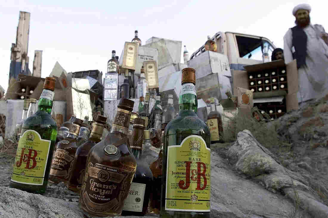 Bottles of alcohol are gathered to be smashed by Taliban authorities in Kabul in 2001.