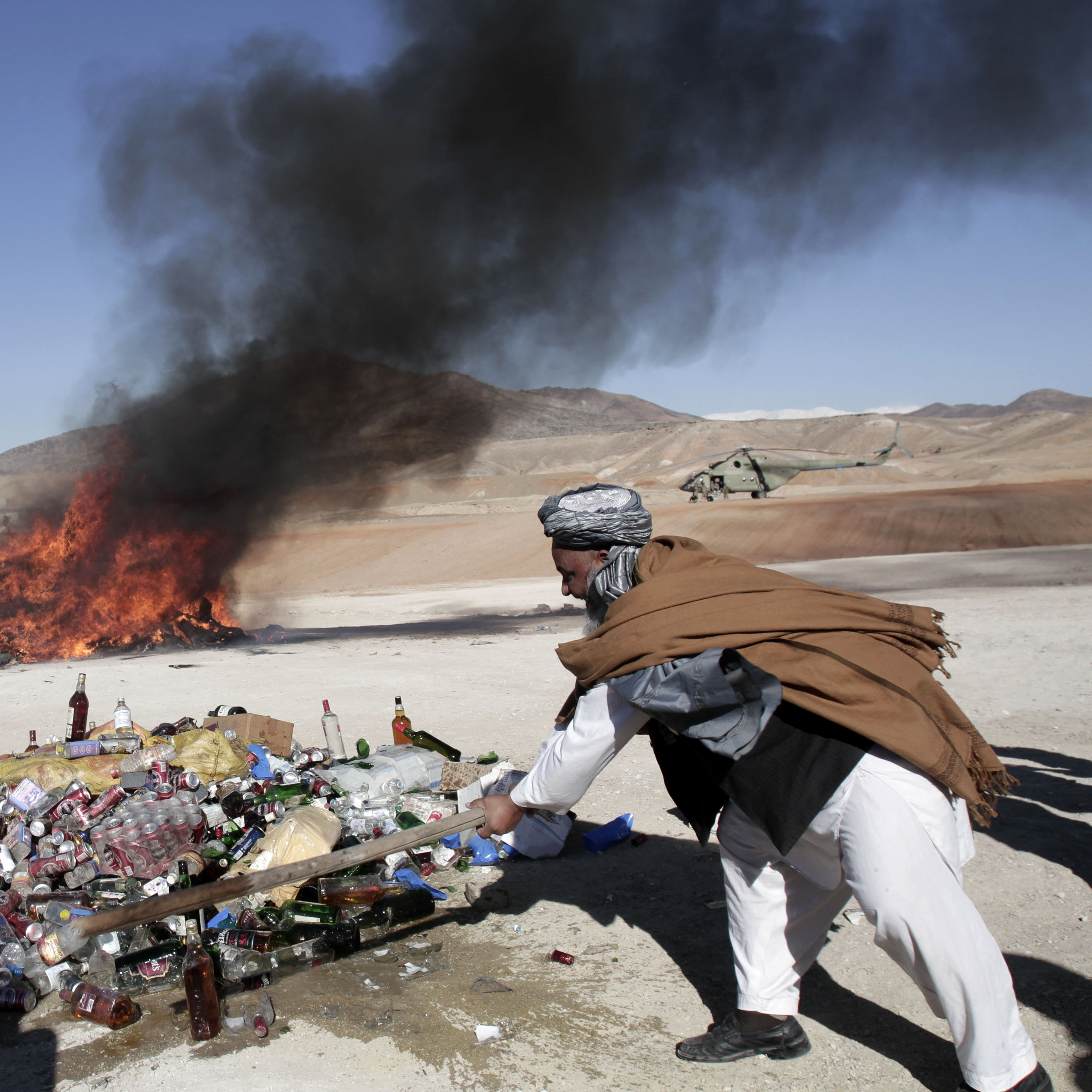 An Afghan man breaks a bottle of alcohol in Jalalabad, east of Kabul, Afghanistan, on Dec. 19, 2012. Authorities destroy confiscated drugs and alcohol in Afghanistan.
