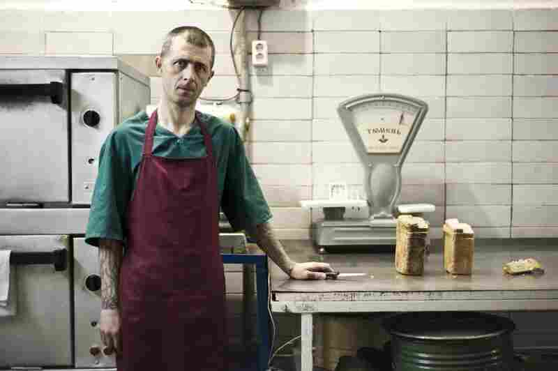 Oleg Pligin is not a prisoner, but works in the institution's bakery. The bread knife is attached to the table by the metal cord.