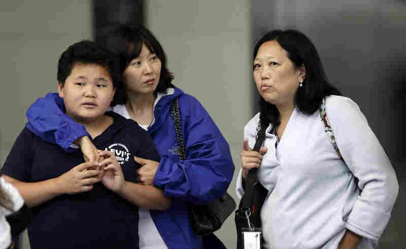 Friends and relatives await updates outside the Reflection Room at the airport.