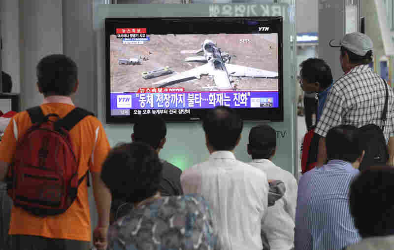 """People watch a news program reporting on the accident at Seoul Railway Station in South Korea. The writing on the screen reads, """"Fire on the ceiling of the airplane."""""""