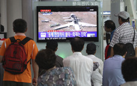 People watch a news program reporting on the accident at Seoul Railway Station in South Korea. The writing on the screen reads,