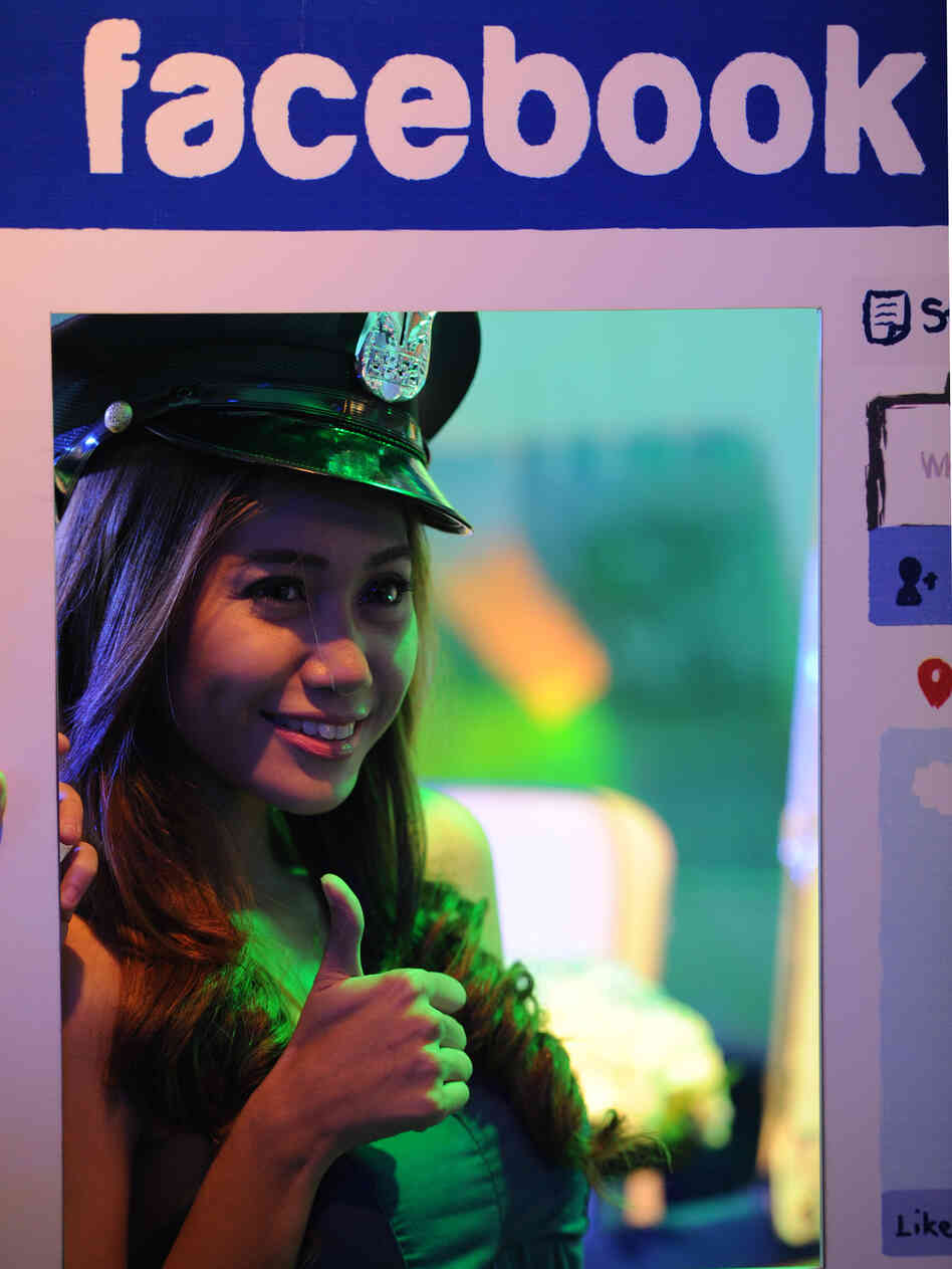 A model poses for photos next to a life-size makeshift Facebook browser in the Philippines.