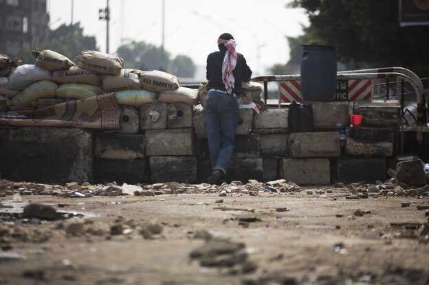 A supporter of Egypt's ousted President Mohammed Morsi stands guard at a barricade near Cairo University, where protesters have installed their camp in Giza, southwest of Cairo, Egypt, on Sunday.