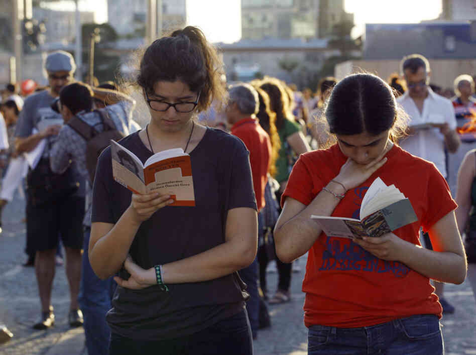 People stand and read books during a silent protest last month at Istanbul's Taksim Square.
