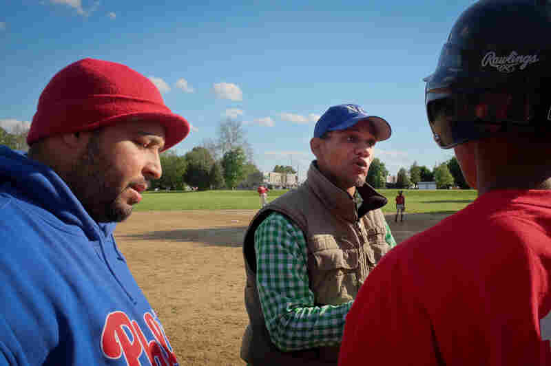 Angel Ramos (left), coach for two of the boys teams, and Bryan Morton (center), president of the league, give a pep talk during a game in Chester, Pa.