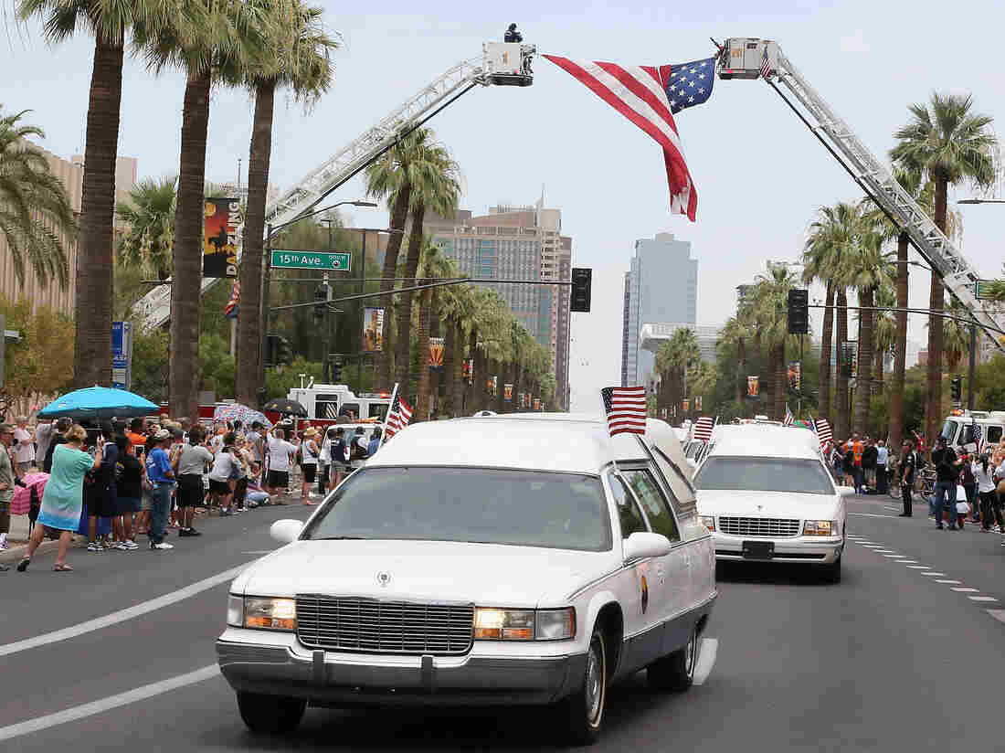 """On Sunday in Phoenix, the 19 bodies of firefighters killed while battling a wildfire in central Arizona were driven to Prescott, where the """"hotshot"""" team was based."""