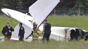 Police and emergency personnel stand near the remains of a fixed-wing aircraft that was engulfed in flames Sunday at the Soldotna Airport in Alaska.