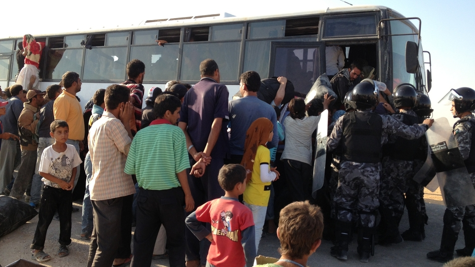Refugees at the Zaatari refugee camp in Jordan try to squeeze on one of the buses heading back to Syria. Syrian refugees have been coming to Jordan for two years, but some are now starting to head home. (NPR)