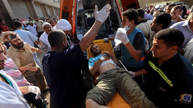 A wounded man is helped from the scene Monday in Cairo after shots were fired during a protest against the ouster of President Mohammed Morsi. (EPA /LANDOV)