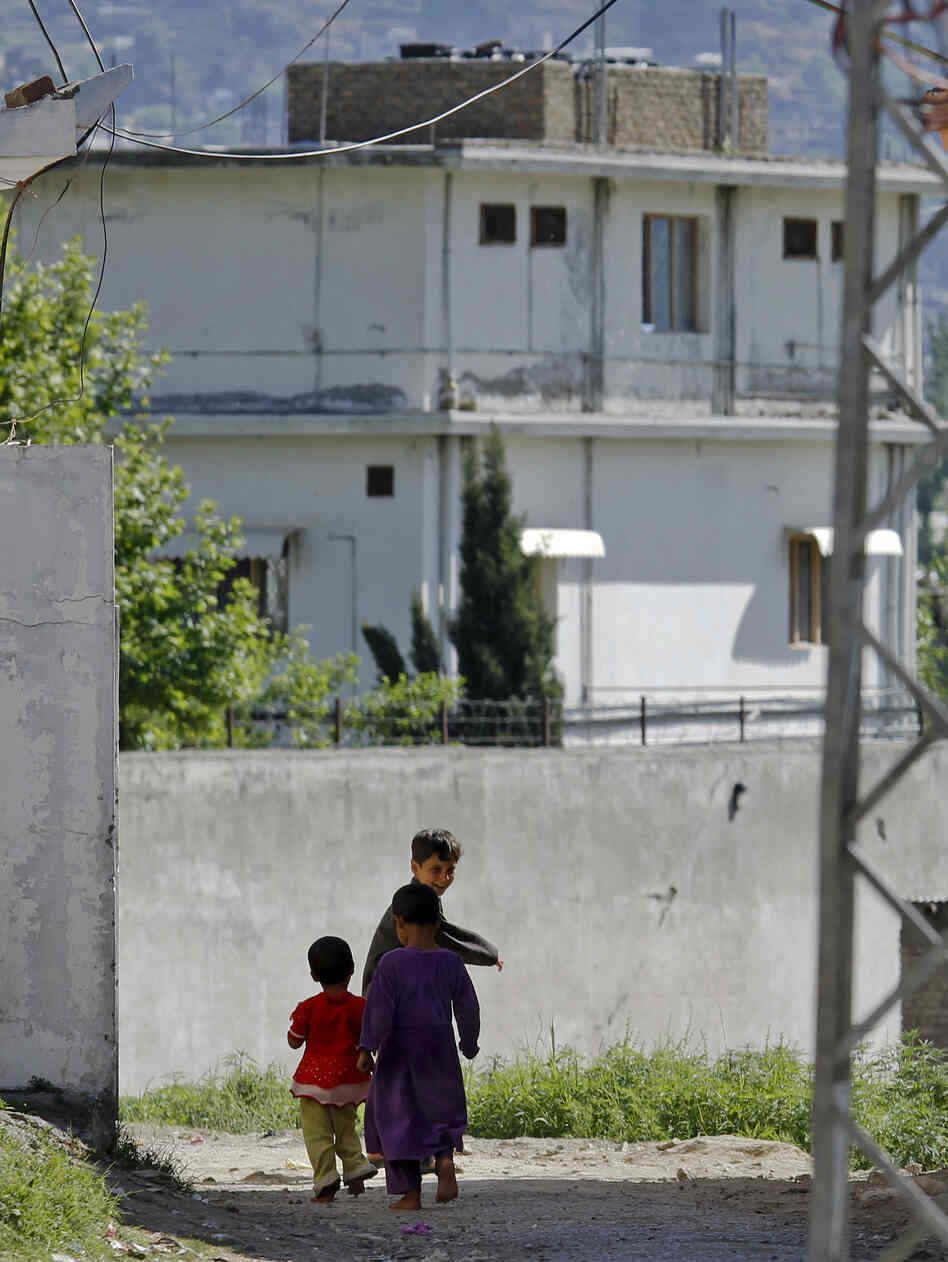 "Children walk past the house of former al-Qaida leader Osama bin Laden in Abbottabad, Pakistan, on May 8, 2011. A new Pakistani report says the ""extent of incompetence"" in failing to detect bin Laden despite the size of the house was ""to put it mildly ... astounding, if not unbelievable."""