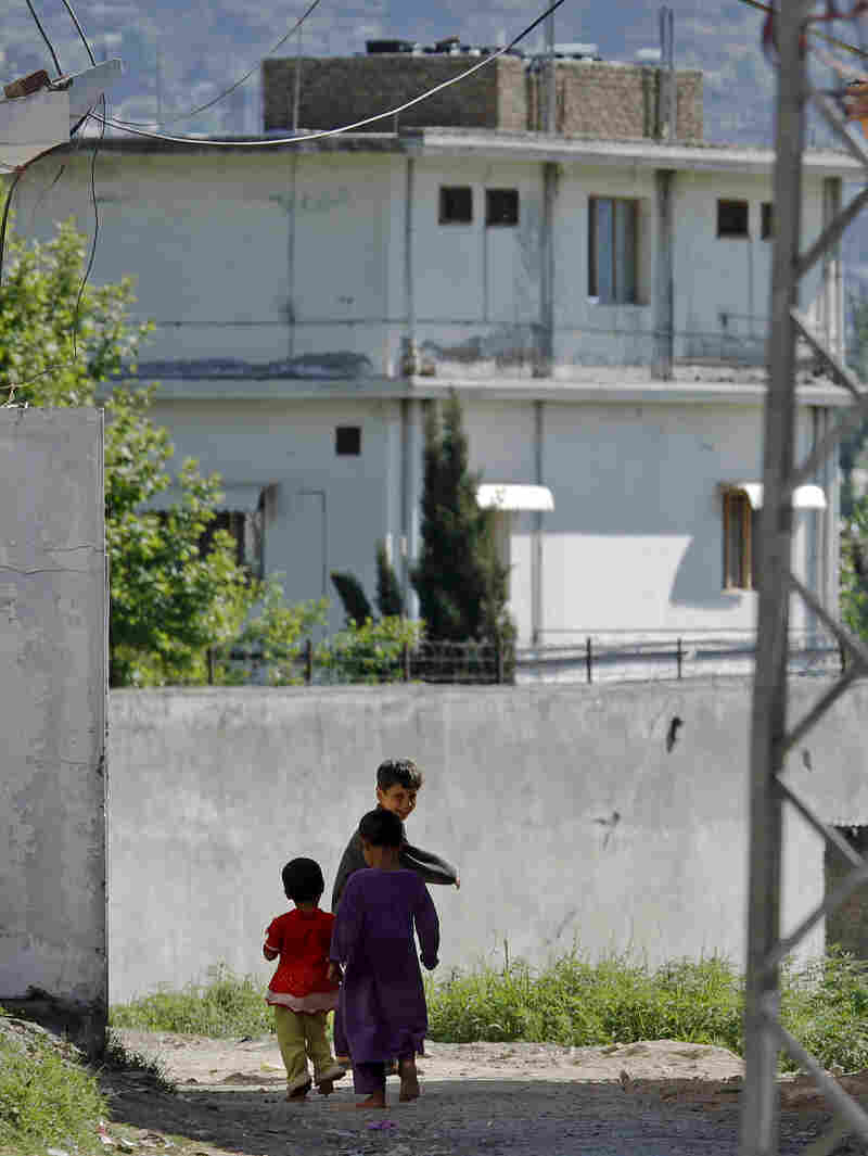 Children walk past the house of former al-Qaida leader Osama bin Laden in Abbottabad, Pakistan, on May 8, 2011. A new Pakistani re