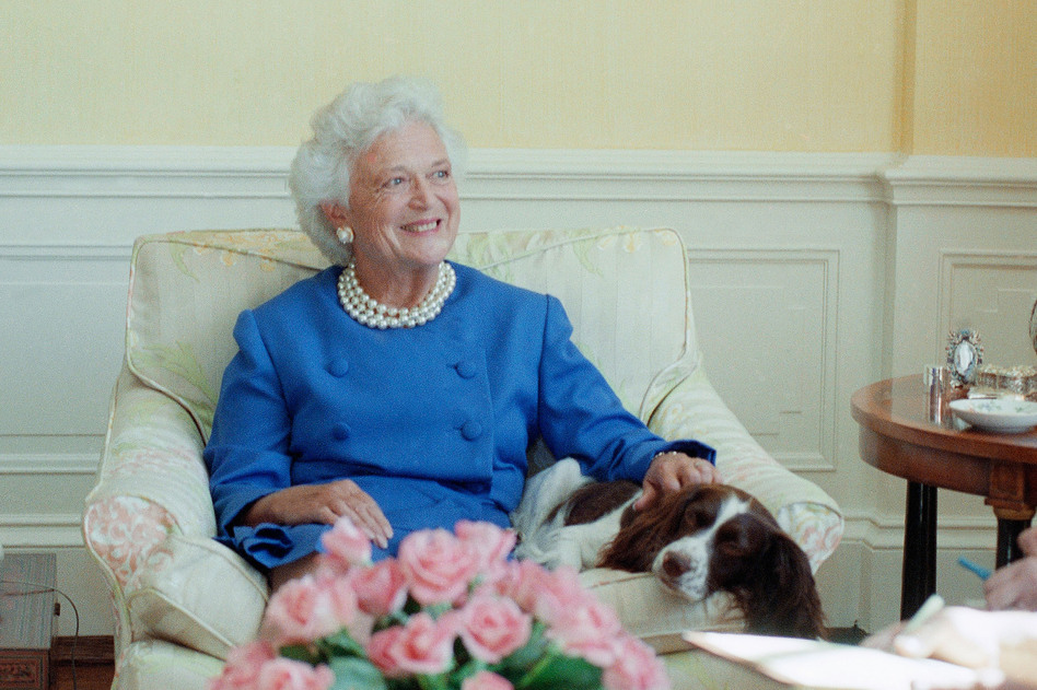 """First lady Barbara Bush, with her pet dog Millie, talks to reporters in September 1990 in Washington, D.C. Mrs. Bush said Iraq cannot be allowed to get away with its occupation of Kuwait. She also revealed that Millie has a case of lupus but """"she's in complete remission."""" (Charles Tasnadi/AP)"""