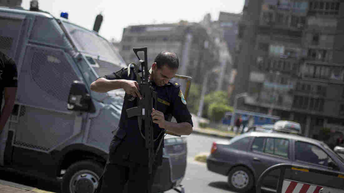 A member of Egypt's police special forces stands guard next to an armored vehicle on July 3, protecting a bridge between Cairo's Tahrir Square and Cairo University where Muslim Brotherhood supporters gathered.