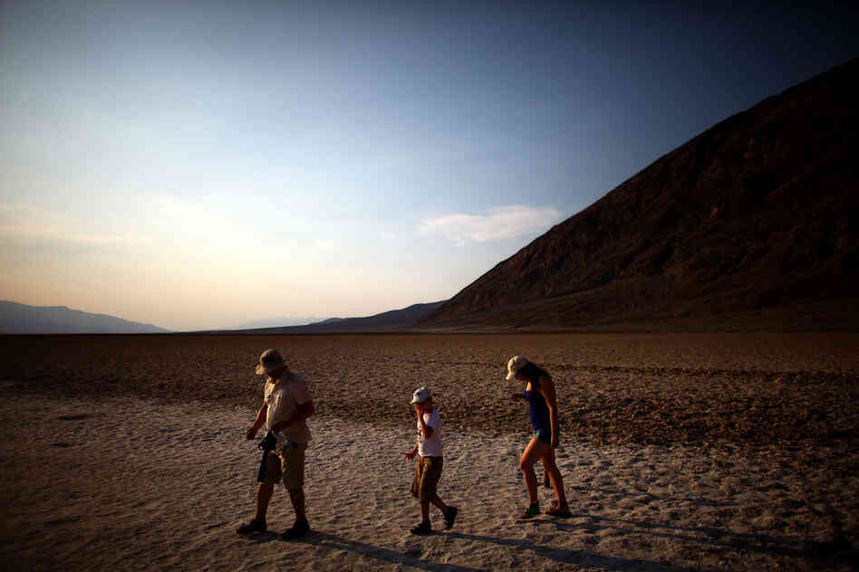 Tourists walk across the Badwater Basin, which sits 282 feet below sea level, in Death Valley, Calif., on June 30. People from around the world flock to the area to experience temperatures that rise to the high 120s on a regular basis.