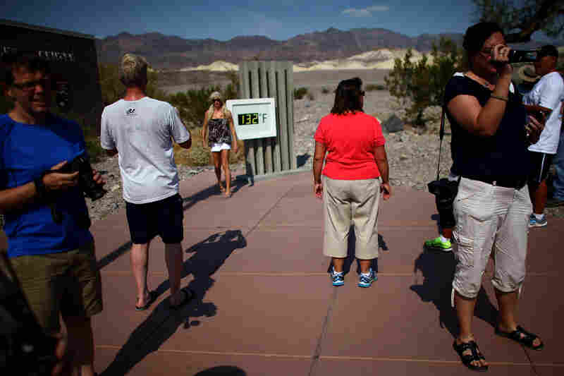 A crowd gathers at the temperature gauge outside the Furnace Creek Visitors on June 30. The temperature on the official thermometer was at 129 degrees in the shade.