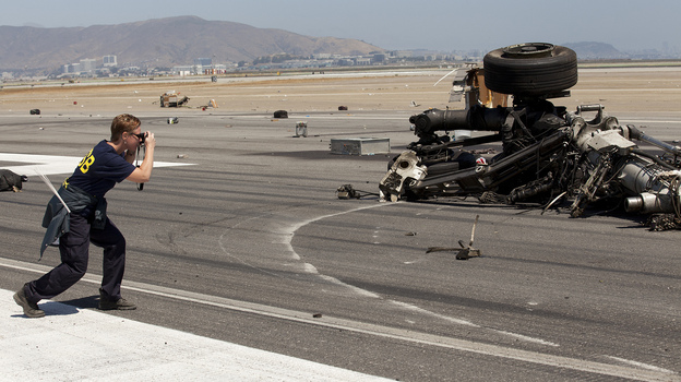 The pilot who attempted to land Asiana Airlines Flight 214  in San Francisco , says the National Transportation Safety Board. Here, a member of the team investigating the crash-landing takes a photo of the plane's landing gear. (Flickr)