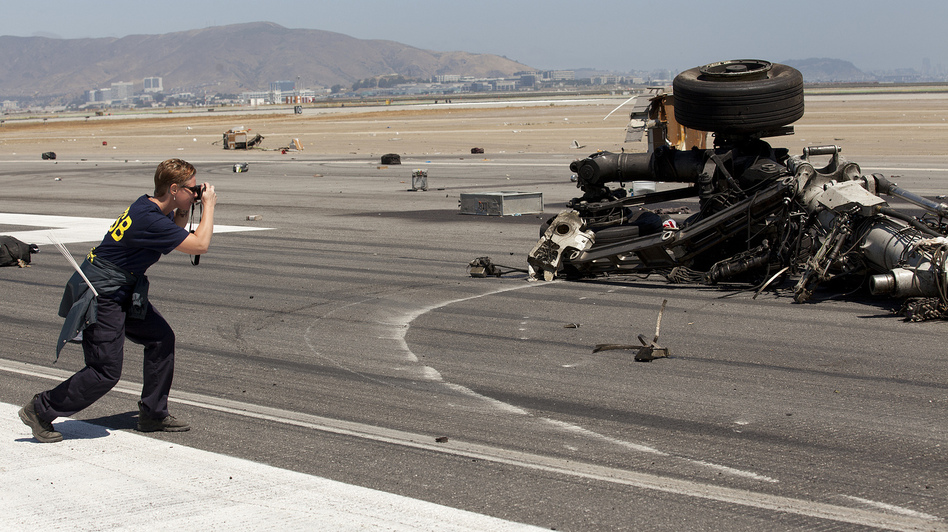 The pilot who attempted to land Asiana Airlines Flight 214  in San Francisco , says the National Transportation Safety Board. Here, a member of the team investigating the crash-landing takes a photo of the plane's landing gear.