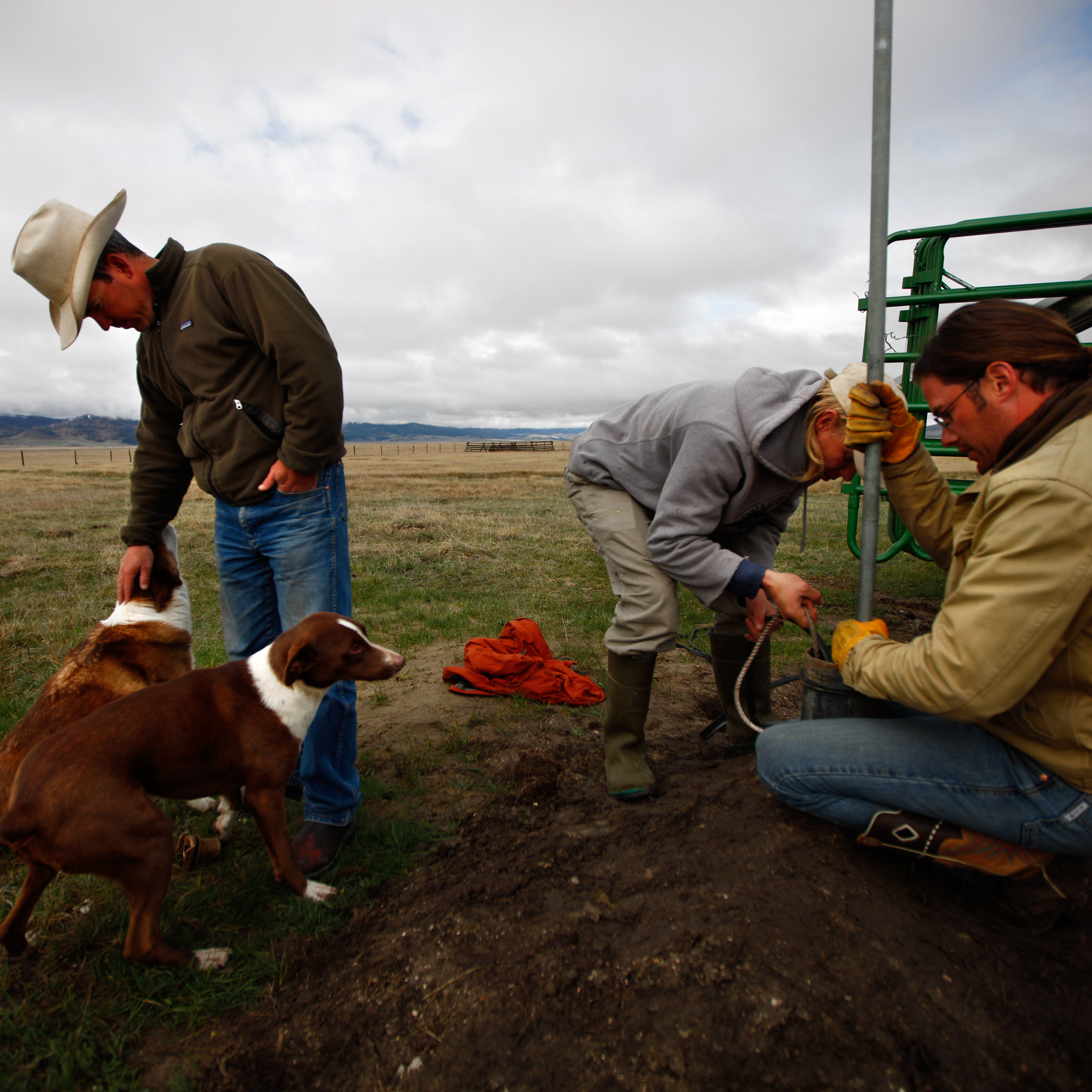 Bryan Ulring (left), ranch hand Graham Fulton (right) and Nature Conservancy ecologist Nathan Korb (center) install a pipe on a new well dug for the cattle Ulring manages for J Bar L Ranch. The ranch is working with The Nature Conservancy to try to preserve sage grouse habitat.