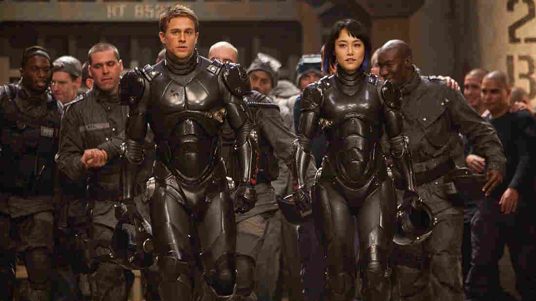 Charlie Hunnam and Rinko Kikuchi are the human co-pilots who mind-meld to control the giant Jaegers — massive robots engineered to fight rampaging sea monsters — in Pacific Rim, a kaiju-film homage from director Guillermo del Toro.