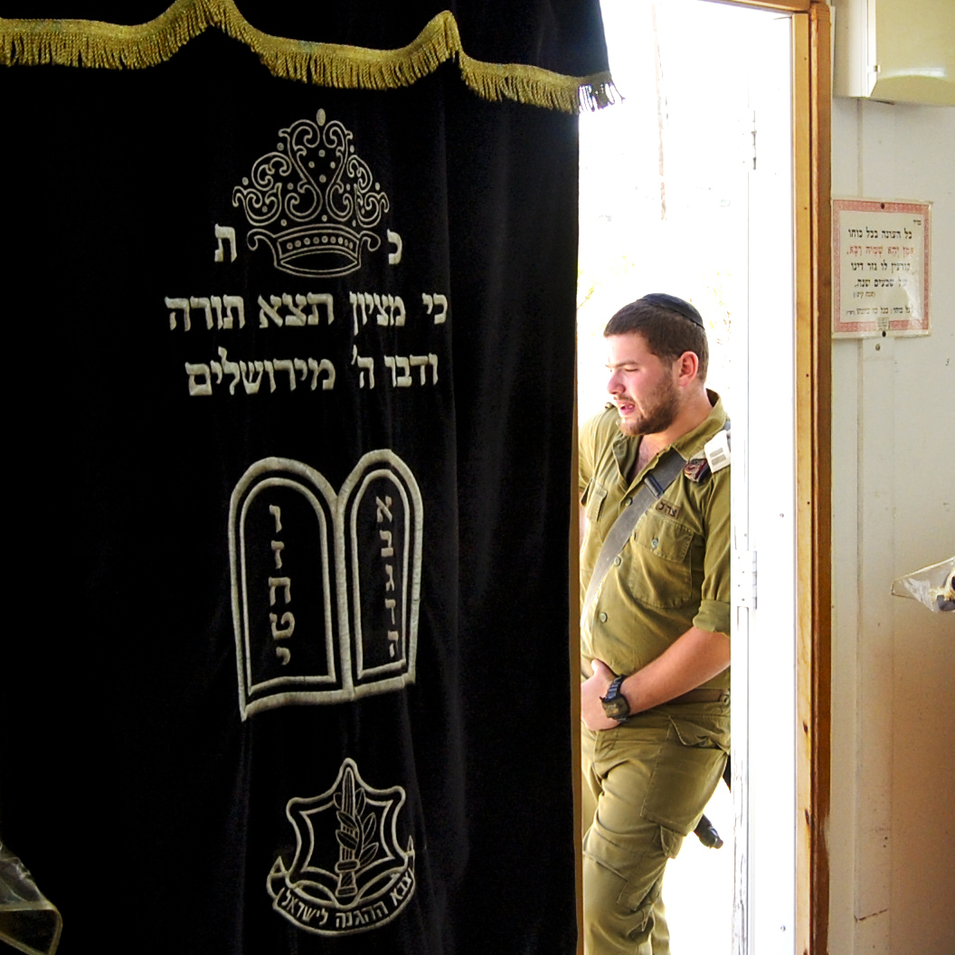An Israeli soldier in a platoon reserved for the ultra-Orthodox leans on the doorway of the unit's makeshift synagogue. The military accommodates the religious needs of ultra-Orthodox soldiers by allowing time for Torah study and prayers three times daily.