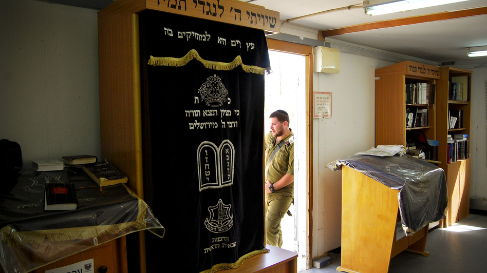 An Israeli soldier in a platoon reserved for the ultra-Orthodox leans on the doorway of the unit's makeshift synagogue. The military accommodates the religious needs of ultra-Orthodox soldiers by allowing time for Torah study and prayers three times daily. (Emily Harris/NPR)