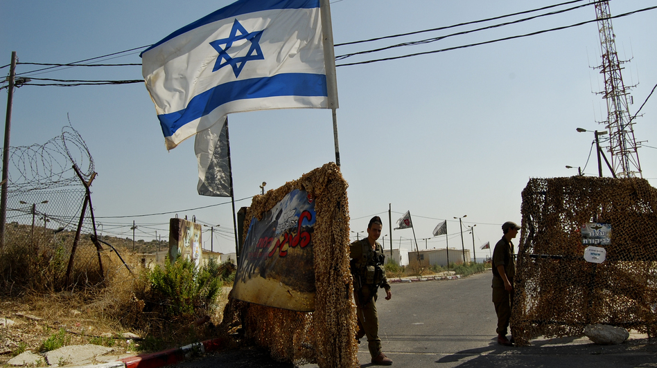 Soldiers close the gate to the tiny West Bank outpost, right next door to a Jewish settlement, where the HaHod platoon of the ultra-Orthodox Netzah Yahuda battalion is stationed. (Emily Harris/NPR)