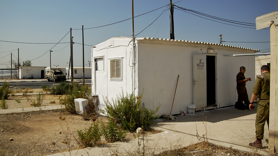 A white metal trailer serves as the makeshift synagogue at the West Bank outpost of an all-ultra-Orthodox Israeli military platoon. (Emily Harris/NPR)