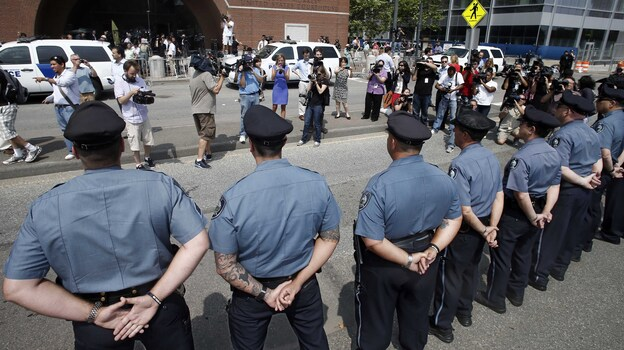 MIT police officers stand at attention outside a federal courthouse where Boston Marathon bombing suspect Dzhokhar Tsarnaev pleaded not guilty to 30 counts today.  He is also accused in the death of MIT officer Sean Collier. (AP)