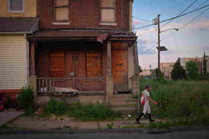 """Angel Ramirez, a North Camden Little League player, walks through the Sixth Street drug corridor, known as """"Heroin Highway,"""" on his way home from practice in Camden, N.J. The Little League program is aimed at keeping kids in the struggling city engaged in a sport after school."""
