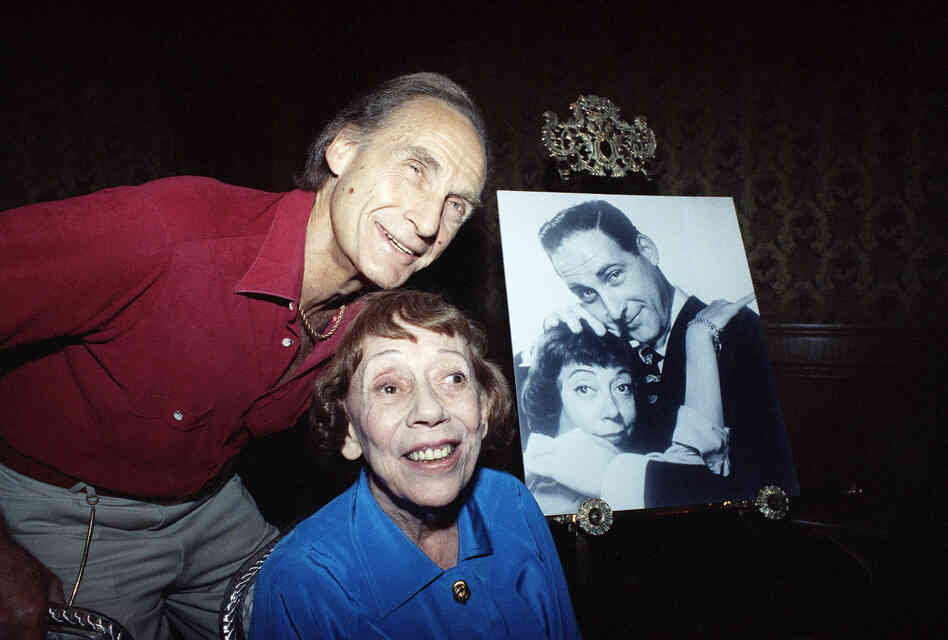 Legendary pair Caesar and Coca pose in a Boston hotel in 1992, near an old photograph of the two of them. They were announcing the Boston opening of their comedy show Together Again.