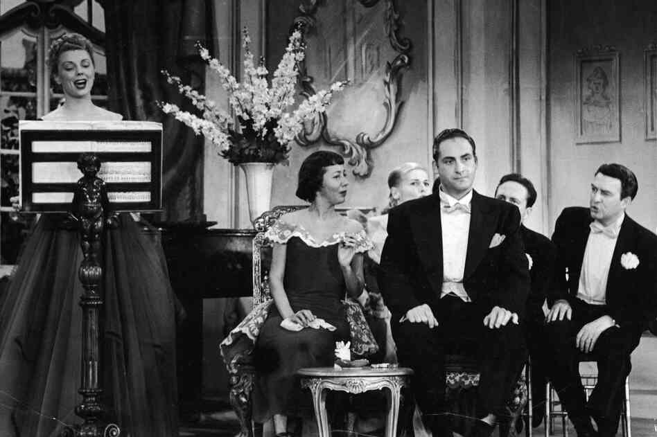 Caesar, flanked by cast performers Imogene Coca and Carl Reiner, listens to a singer in a skit from the TV comedy series Your Show of Shows, in 1952.