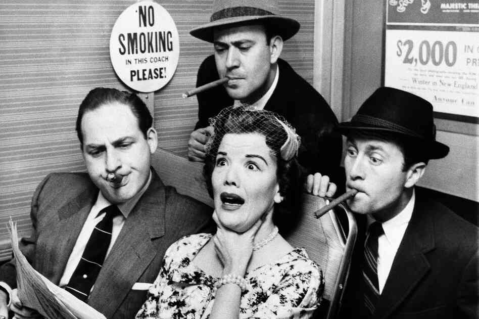 Nanette Fabray gags as railroad commuters Caesar, Carl Reiner (top) and Howard Morris (right) poke their smokes in her direction while looking over her shoulder to read her newspaper, on Caesar's Hour, in 1955.